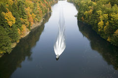 A boat navigates the Connecticut River through autumn color on the Mohawk Trail of western Massachusetts, New England Stock Images