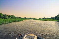 Boat navigating through flooded waters of Pantanal at sunset Royalty Free Stock Photos