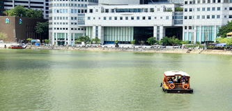 A boat is navigating the singapore river. That pass through the CBD Stock Image
