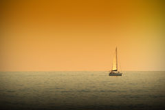 A boat navigating a tranquile sea at sunset time. Dark orange atmosphere. Empty copy space for Editor`s text Royalty Free Stock Image