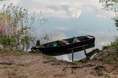 A boat near a bank of the lake. Grass and sky reflection in the water Royalty Free Stock Photo