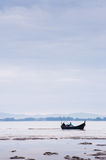 Boat near beach on low tide Royalty Free Stock Image