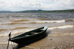 Boat near lake. Image of lake with forest and mounts at the horizon and boat on the shore Stock Photography