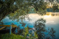 Boat near lake at dawn. Lake landscape at sunrise, beautiful nature dawn Royalty Free Stock Image