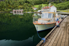 Boat near a mooring, Norway. The white yacht/boat near a mooring, the yacht is reflected in aurlandsfjord water. Photo made in Flam, Norway stock photos