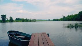 Boat near pier on pond. Boat near wooden pier on fishing pond. Timelapse stock footage