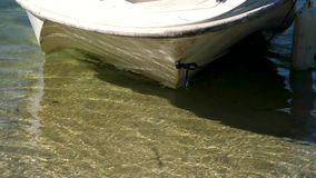 Boat near shore , crystal clear water. Boat swims up to the shore of the lake so the people went ashore.  stock video