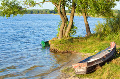 Boat near the summer lake shore. Old wooden fishing boat near the summer lake shore (Svityaz, Ukraine Stock Image