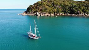 Boat near tropical shore. Amazing drone view of modern yacht sailing on calm sea water near coast of tropical volcanic stock video footage