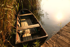 Boat near wooden path on lake Stock Photography