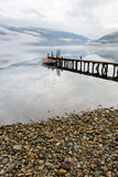 Boat near wooden pier in a norwegian lake. Boat near wooden pier in a norwegian fiord in cloudy weather. Amazing nature of Norway royalty free stock photography
