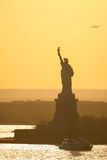 Boat next to Statue of Liberty Stock Photo