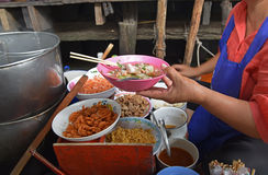 Boat noodle is a Thai style noodle dish originally served from boats that traversed Bangkok's canals. In this picture, the boat vendor is preparing the dish on stock photos