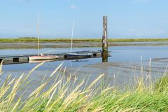 Boat on the North Sea. With blue sky and gras in front Royalty Free Stock Photo