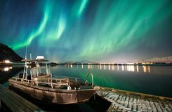 Boat with northern lights background. In Lofoten Islands, Norway royalty free stock photo