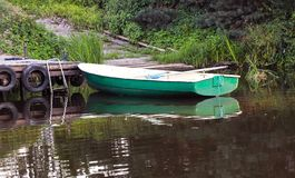 Boat with oars near the pier. Summer on the lake stock images