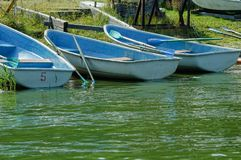Boat with oars on the river bank. Blue wooden sailing boats with oars at the banks of river Stock Photography
