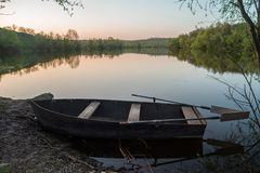 Boat with oars on the river shore at sunset. Selective focus stock photos