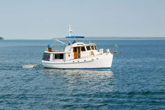 Boat on the ocean. A small boat on the ocean, pulling a row boat Stock Photos