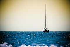 Boat in ocean. Boat in sunset ocean with sails down Royalty Free Stock Photography