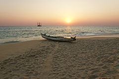 Boat on the ocean shore at sunset. Kerala, India Stock Photography