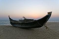 Boat on the ocean shore at sunset. Kerala, India Stock Photo