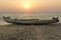 Boat on the ocean shore at sunset. Kerala, India Royalty Free Stock Image