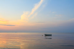 Boat in the ocean at sunrise. Sunset with beautiful sky Royalty Free Stock Photography
