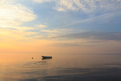 Boat in the ocean at sunrise Royalty Free Stock Images