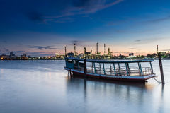 Boat with Oil refinery at twilight Stock Photography