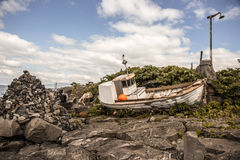 Boat. Old , Abandoned boat on the shore of the Arctic Ocean , around rocks and debris Royalty Free Stock Photos