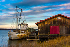 Boat and old building on the shore of the Chesapeake Bay, in St. Stock Image