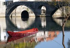 Boat, old house & bridge, reflections on calm water. stock photography