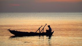 Boat on open sea sunset horizon. The boatman in the Vietnamese hat in the small boat. The man fishes at sunset. Close up. On this video you can see as the small stock video