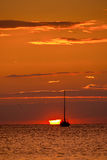 Boat at orange sunset. Orange sunset on the horizon with the silhouette of the ship and the Great Sun Stock Photos