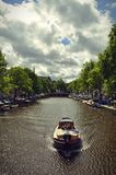 Boat over the canal, Amsterdam. View of a fishing boat cruising on the Herengracht canal of Amsterdam, in front of a cloudy sky Stock Photos