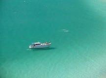 Boat over a crystalline turquoise beach. In Arraial do Cabo, Rio de janeiro, Brazil stock image