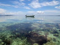Boat over a shallow coral reef Royalty Free Stock Photo