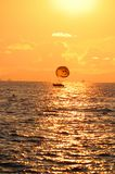 Boat with a parachute at sunset Stock Image