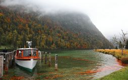 Boat parking on Lake Konigssee with wooden pier and fallen leaves by lakeside on a misty foggy morning. ~ Beautiful autumn scenery of Koenigssee (King's lake) royalty free stock photography