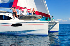 Boat party. Sailboat in the open sea with sailing crew partying on the deck Royalty Free Stock Images