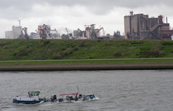 A boat passes heavy industry in Hoek van Holland Stock Photography