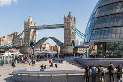Boat passes through Tower Bridge's open drawbridge. LONDON, UK - MARCH 25, 2016: Tourists by City hall watch a boat pass through Tower Bridge's open draw bridge Stock Photos