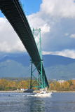 A boat passes under Lion's Gate Bridge. A yacht sails beneath the Lion's Gate Bridge in Vancouver, BC stock images