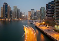 Boat Passing in the Canal of Dubai Marina in the Dusk Royalty Free Stock Photography