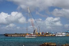 Boat passing in front of a crane on Grand Cayman. Boat passing in front of a crane on the quay on Grand Cayman, Cayman Islands Royalty Free Stock Image