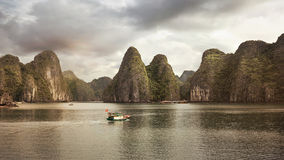 Boat passing in front of mystical hills in Halong Bay Royalty Free Stock Image