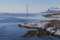 Boat passing the Tjeldsundet strait which separates the mainland stock photography