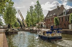 Boat passing by a tree-lined narrow canal with a raised bascule bridge in the sunrise at Weesp. stock photo