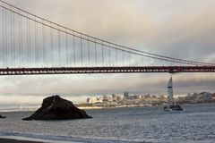 A boat passing under the famous Golden Gate Bridge Royalty Free Stock Image